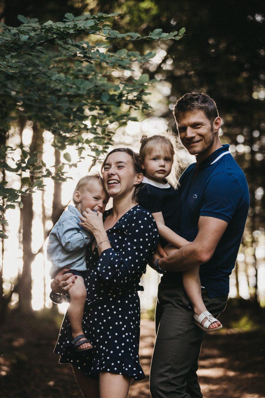 Photo de famille en forêt avec de beaux flous et de belles lumières du soleil couchant